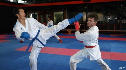 This picture taken on May 11, 2021 shows Afghan-born refugee and karate competitor Asif Sultani (L) training on the outskirts…