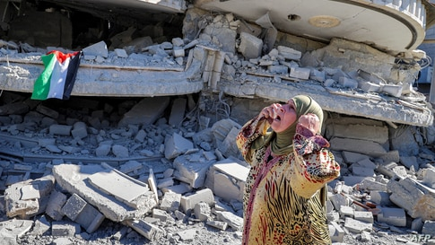A Palestinian woman reacts outside a building that belonged to Montasser Shalabi, who was arrested in May on suspicion of…