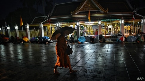 A Buddhist monk walks past people queueing overnight for free Covid-19 swab testing at Wat Phra Sri Mahathat Woramahawihan in…
