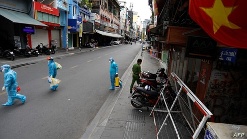 Medical workers collecting test samples from residents walk past in Ho Chi Minh City on July 9, 2021, on the first day of the…
