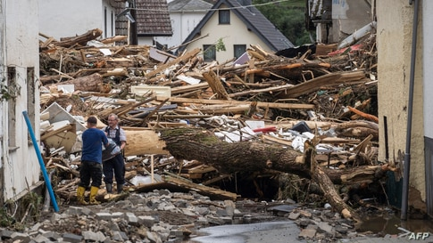 Two men remove try to secure goods from next to debris of houses destroyed by the floods in Schuld near Bad Neuenahr, western…