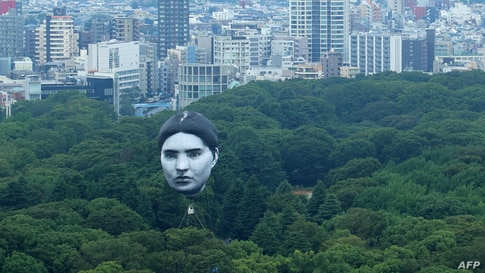 """A hot air balloon created by Japanese art group """"mé"""" floats over Tokyo's Yoyogi Park on July 16, 2021, part of a project called…"""