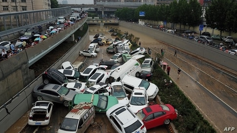 An aerial view shows cars sitting in floodwaters at the entrance of a tunnel after heavy rains hit the city of Zhengzhou in China's central Henan province.