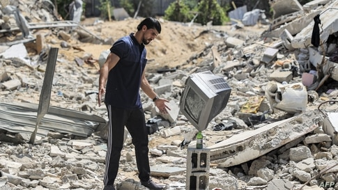 Palestinian performance artist Mohammed al-Shenbari stacks up a television atop a bottle as he demonstrates his skills in balancing objects, in the ruins of houses in Beit Lahia in the northern Gaza Strip, July 6, 2021.