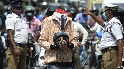 Police officers along with a volunteer (C) dressed up as a motorcyclist holding a mockup head with a helmet take part in a road safety awareness campaign, in Chennai, India.