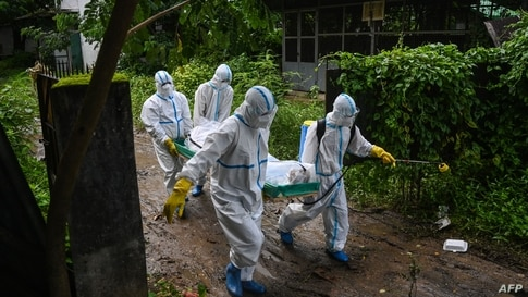 Volunteers wearing personal protective equipment carry the body of a victim of the Covid-19 to a cemetery in Hlegu Township in Yangon, Myanmar, July 10, 2021.