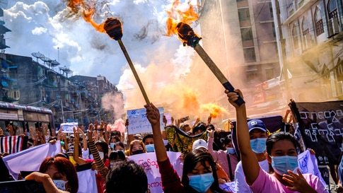 Women carry burning torches as they march during a demonstration against the military coup in Yangon, Myanmar.