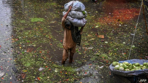 A worker carries vegetables as he wades through a waterlogged street in a market area in Lahore, Pakistan.