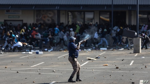 A member of the South African Police Services (SAPS) fires rubber bullets at rioters looting the Jabulani Mall in Soweto, southwest of Johannesburg.