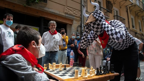 """People play chess in Estafeta street in Pamplona, Spain, during the """"Chess Run"""" tournament."""
