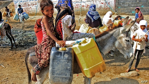 Children riding on donkeys queue to fill their jerrycans with water from a cistern at a make-shift camp for the internally displaced in Yemen's northern Hajjah province amid extreme heatwave and severe water shortage.