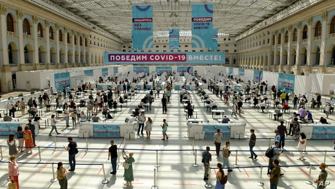 People wait in line for a COVID-19 vaccine at a vaccination center in Gostinny Dvora huge exhibition place in Moscow, Russia,…