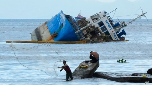 A fisherman throws his net beside the half-submerged M/V Palawan Pearl after it collided with a Cyprus-flagged BKM 104 dredger…