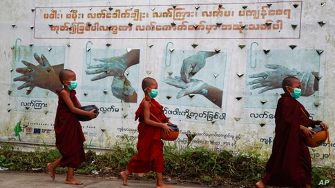 Buddhist novice monks wearing face masks walk past a COVID-19 awareness sign as they collect morning alms Thursday, July 15,…
