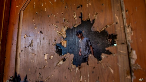 A Kashmiri, inspecting a house where suspected rebels had taken refuge, is seen through a hole created by a mortar shell fired…