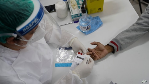 A health worker gives a resident a COVID-19 test on the first day of a three-day vaccination campaign for people over age 35 in the Complexo da Maré favela of Rio de Janeiro, Brazil, July 29, 2021.