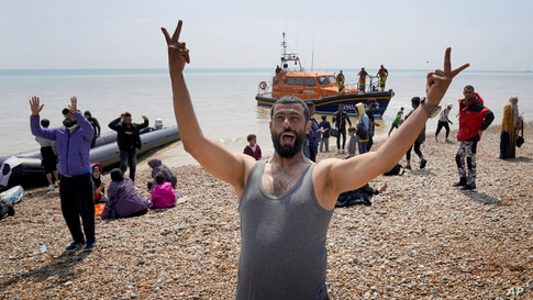 A man gestures as people thought to be migrants stand on the beach after arriving on a small boat at Dungeness in Kent, England.