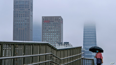 A woman walks on an overhead bridge in the Central Business District in Beijing, on a rainy day.