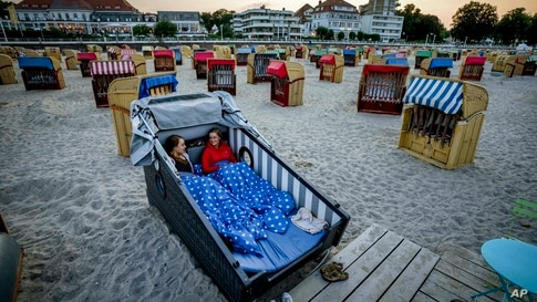 Two young women prepare to spend the night in a specially designed beach chair at the beach of the Baltic Sea in Travemuende, Germany, July 18, 2021.