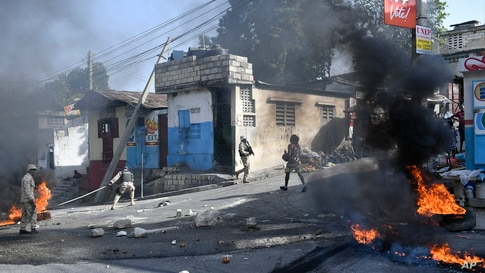 Tires burn after being set on fire by protesters upset with growing violence as police patrol and try to put out the flames and clear the road for vehicles in the Lalue neighborhood of Port-au-Prince, Haiti.