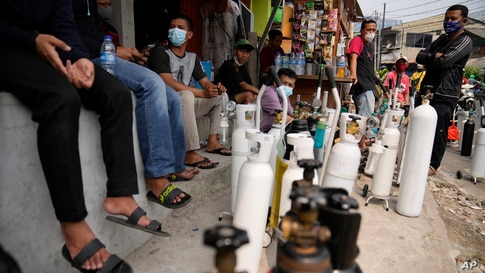People queue to refill their oxygen tanks at a filling station in Jakarta, Indonesia.