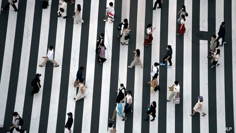 People wearing protective masks to help curb the spread of the coronavirus walk along a pedestrian crossing in Tokyo, Japan.