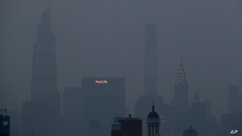 The Met Life and Chrysler buildings glow through a thick haze hanging over Manhattan in New York, July 20, 2021.