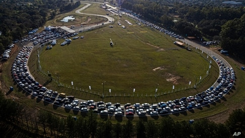 People line up at a drive-thru vaccination center at the Ruben Dumot Autodrome for Pfizer's COVID-19 vaccine in Capiata, Paraguay.