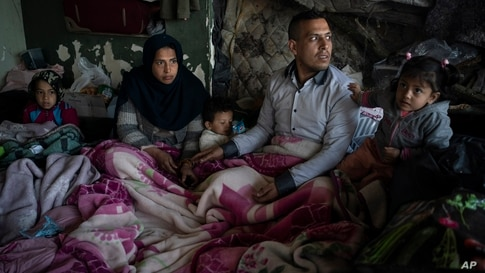FILE - A family from Afghanistan gather at an abandoned building in Edirne, near the Turkish-Greek border, March 6, 2020.