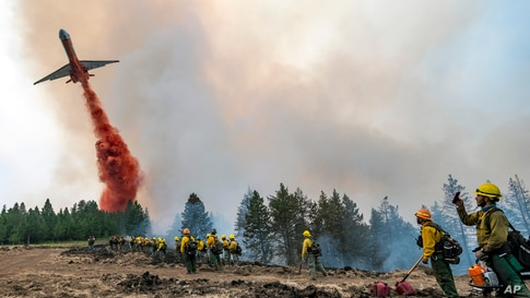 Wildland firefighters watch and take video with their cellphones as a plane drops fire retardant on Harlow Ridge above the Lick Creek Fire, southwest of Asotin, Washington, July 12, 2021.