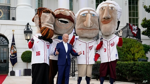 """President Joe Biden is seen with members of the Washington Nationals baseball team called """"The Racing Presidents"""" after speaking at an Independence Day celebration on the South Lawn of the White House, July 4, 2021, in Washington."""