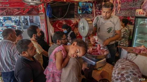 Customers line up at a butcher's shop to buy meat for the holiday, July 19, 2021. (VOA/Hamada Elrasam)