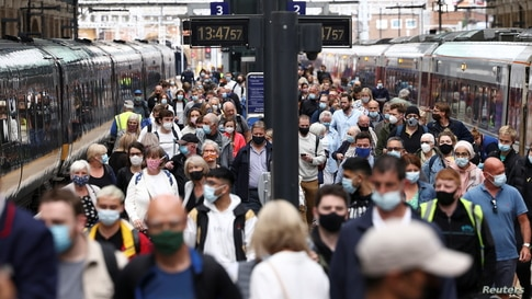 People wearing protective face masks waaPeople wearing protective face masks walk along a platform at King's Cross Station in London.lk along a platform at King's Cross Station, amid the coronavirus disease (COVID-19)…