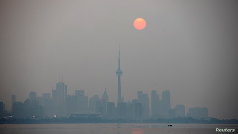 The sun rises through a cover of wildfire smoke above the CN Tower and downtown skyline in Toronto, Ontario, Canada.