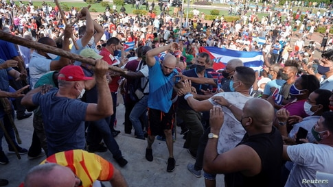 People clash with plain clothes police during protests against and in support of the government, amid the COVID-19) outbreak in Havana, Cuba, July 11, 2021.