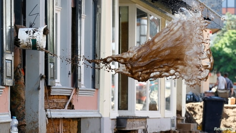A soldier throws water out of a house, following heavy rainfalls, in Bad Muenstereifel, North Rhine-Westphalia state, Germany.