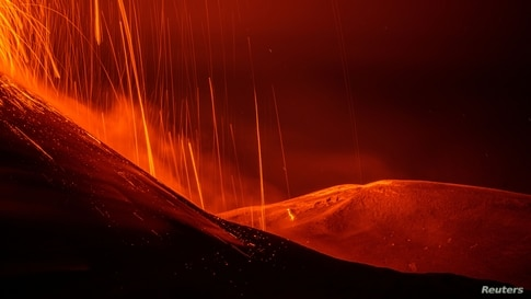 Streams of red hot lava flow as Mount Etna, Europe's most active volcano, erupts, as seen from Sant'Alfio, Italy.