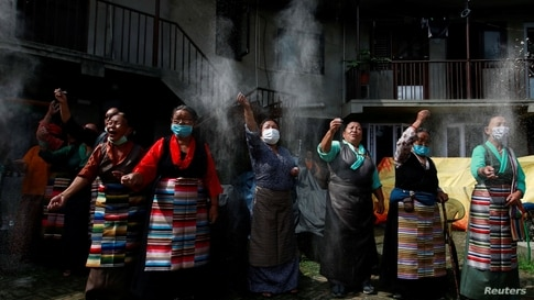 Tibetans dressed in traditional attire perform rituals to mark the 86th birthday celebration of Dalai Lama in Lalitpur, Nepal, July 6, 2021.