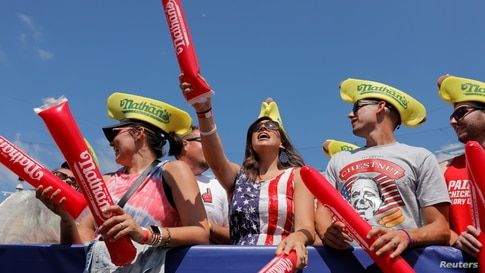 People cheer ahead of the Nathan's Famous Fourth of July Hot Dog-Eating Contest held on Independence Day at Maimonides Park in Brooklyn, New York City.