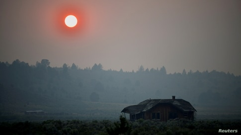 Thick smoke causes the sun to glow red over an abandoned farmhouse as the Bootleg Fire expands to over 200,000 acres, near Beatty, Oregon, July 13, 2021.
