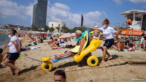 Disabled Manuel Molina, 80, sits on an amphibious chair as he is helped by lifeguards Olga Diaz and Micaela before swimming in the Mediterranean sea, on Barcelona's Nova Icaria Beach, Spain.