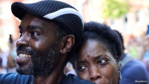 """Tanya and Evance Chanda from Mechanicsville look on as a statue of Confederate General Thomas """"Stonewall"""" Jackson is removed after years of a legal battle over the contentious monument, in Charlottesville, Virginia, July 10, 2021."""