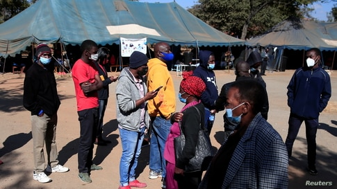 FILE - People queue to recieve COVID-19 vaccinations at a clinic in Harare, Zimbabwe, July 8, 2021.