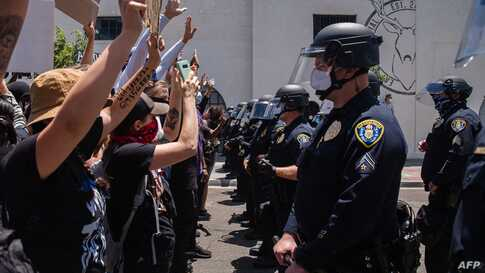 Demonstrators face-off with officers in front of the San Diego Police in downtown San Diego, California on May 31, 2020 as they…