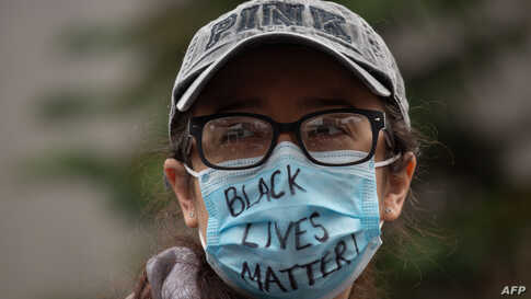 SEATTLE, WA - MAY 31: A demonstrator wears a Black Lives Matter mask during a gathering to protest the recent death of George…