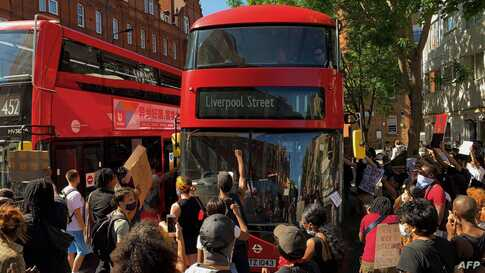 Demonstrators stop a bus as they block the street in Sloane Square in London on May 31, 2020 after marching on the US embassy…