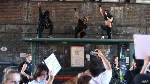 TOPSHOT - Demonstrators stand on top of a bus shelter they march near the US Embassy in central London on May 31, 2020 to…