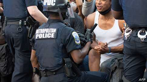 A man screams with emotion as he sees a policeman take a knee while hundreds protest the death of George Floyd next to the…