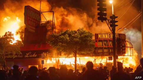 TOPSHOT - Protesters gather in front of a liquor store in flames near the Third Police Precinct on May 28, 2020 in Minneapolis,…
