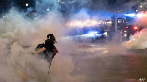 TOPSHOT - A protester hurls a tear gas canister back towards the Detroit police after tensions were sparked by arrests of…